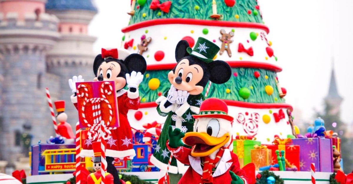 Mickey Mouse, Minnie Mouse und Donald Duck mit Geschenken vor einem riesigen Weihnachtsbaum