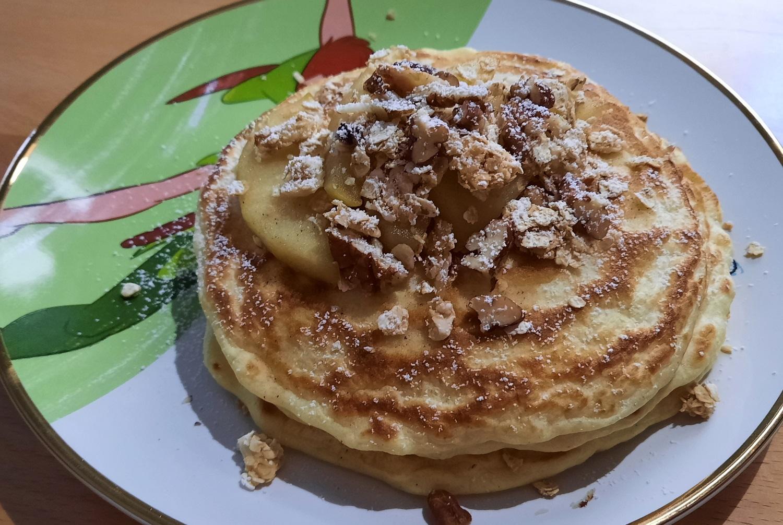 Drei Pancakes mit Apfelspalten, Granola und Pekannüssen auf einem Peter Pan-Teller
