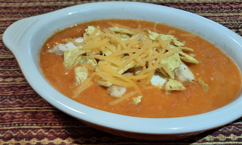 Suppe garniert mit Tortilla Chips, Hähnchenstreifen und Cheddar
