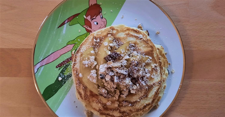 Pancakes mit Apfelspalten und Granola auf einem Teller mit Peter Pan-Motiv