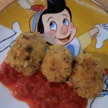 Drei frittierte Risottobällchen sind mit Tomatensauce auf einem Teller mit Pinocchio-Motiv angerichtet