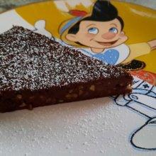 Ein Stück Schokoladen-Haselnuss-Kuchen auf einem Teller mit Pinocchio-Motiv