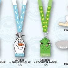Drei Pin-Lanyards und zwei Pins mit Disney-Motiven: Dschinnie, Olaf, Pascal,
