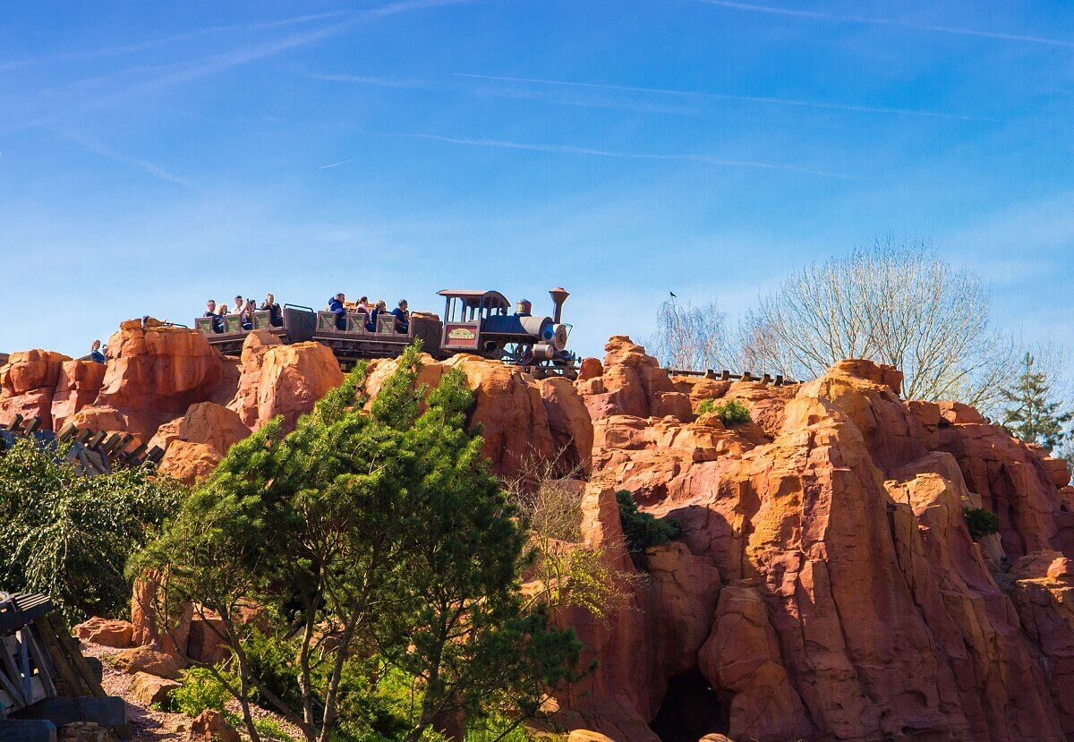 A Big Thunder Mountain roller coaster train drive through the rocky hills