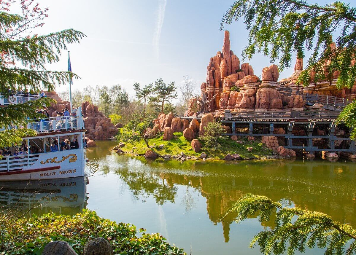 Blick an Pflanzen vorbei auf den inmitten der Rivers of the Far East gelegenen Big Thunder Mountain und den Raddampfer Molly Brown