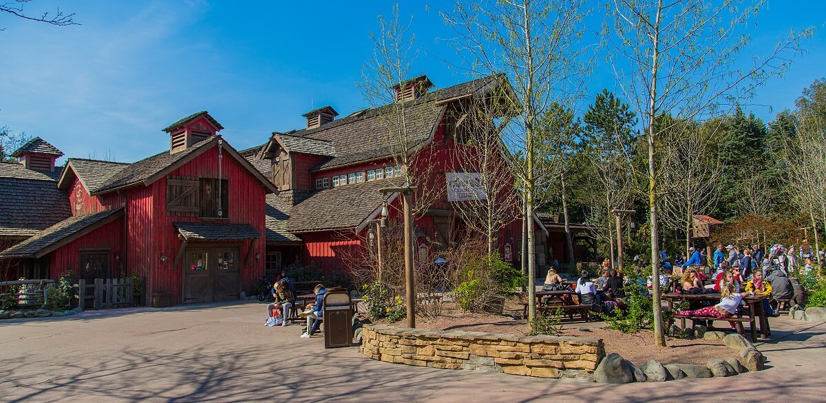 View on the large square with seating area in front of the barn of the Cowboy Cookout Barbecue in Frontierland