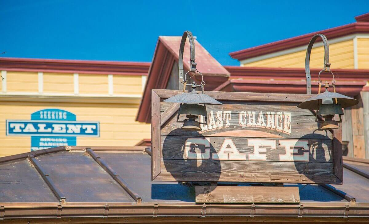 On the canopy of the Last Chance Café there is a large wooden sign with the name of the restaurant