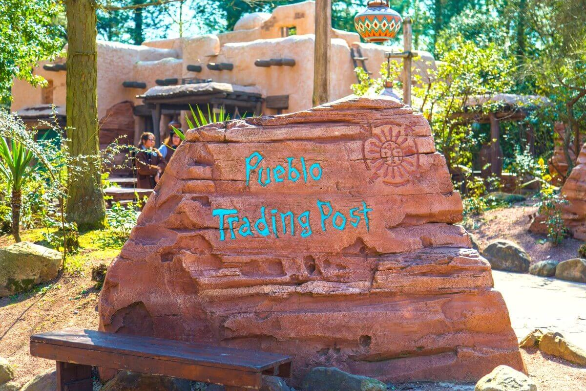 On a red stone is written Pueblo Trading Post in turquoise font