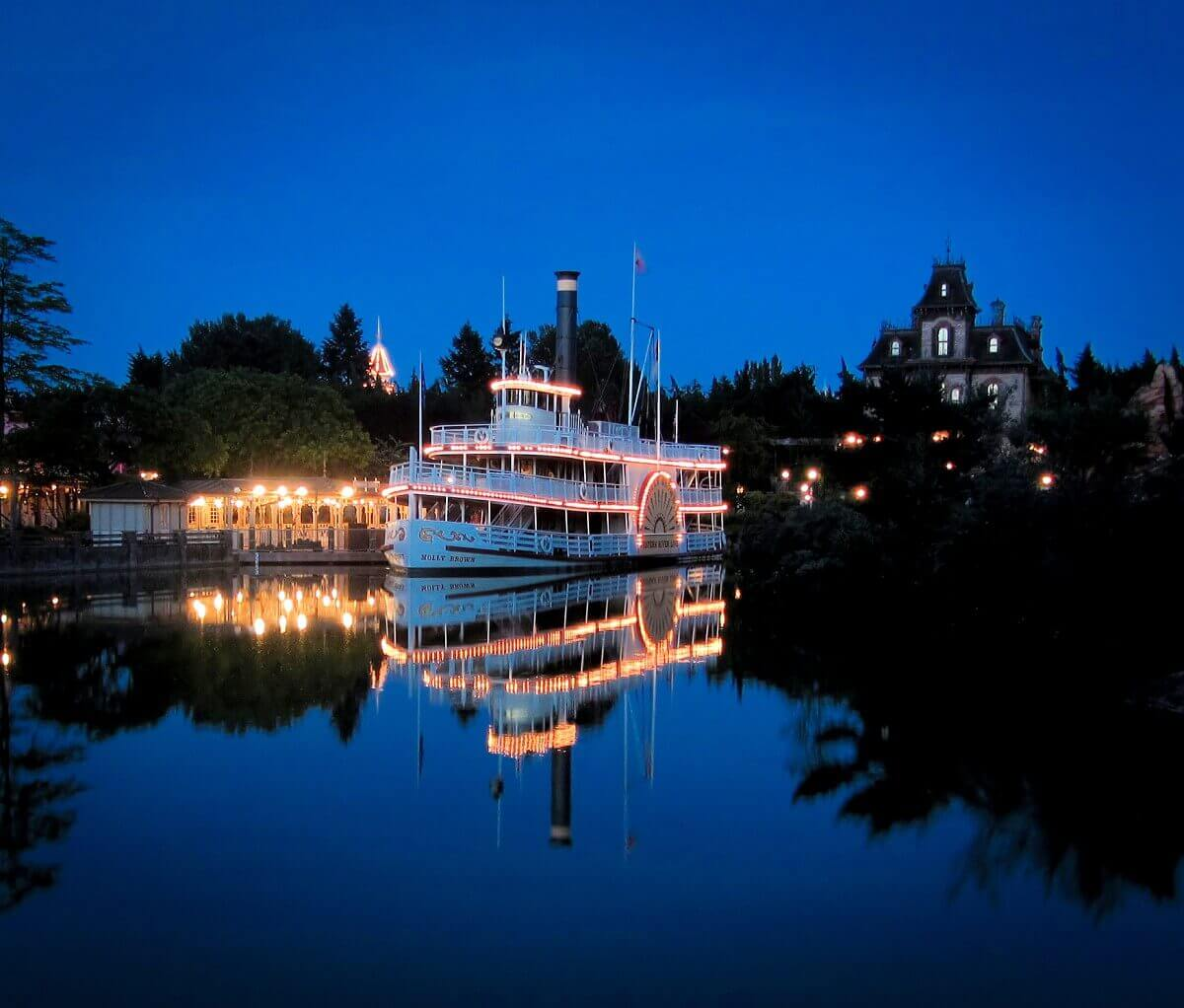 The Steamboat lights up at night, behind it you can see Phantom Manor
