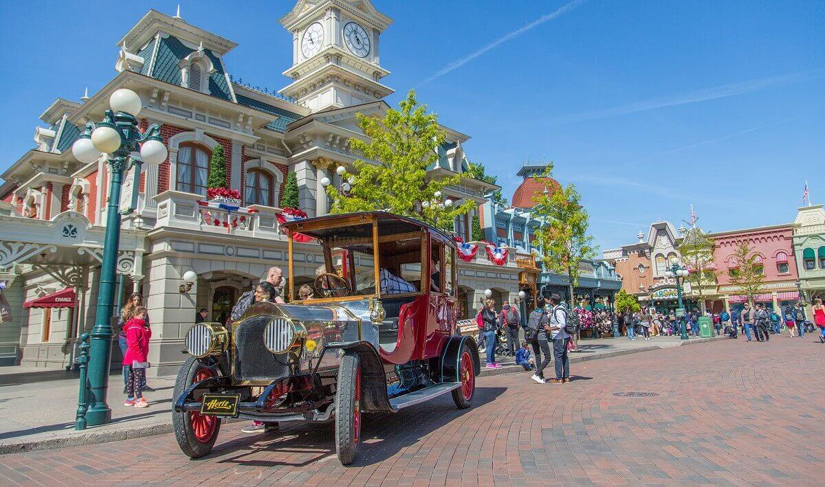 Ein Fahrzeug der Main Street Vehicles steht vor der Town Hall hinter dem Eingang zum Disneyland Park