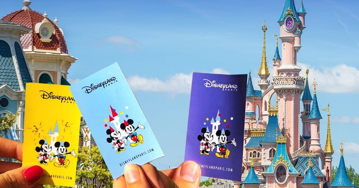 3 tickets for Disneyland Paris in front of the castle. The tickets are held up in the air